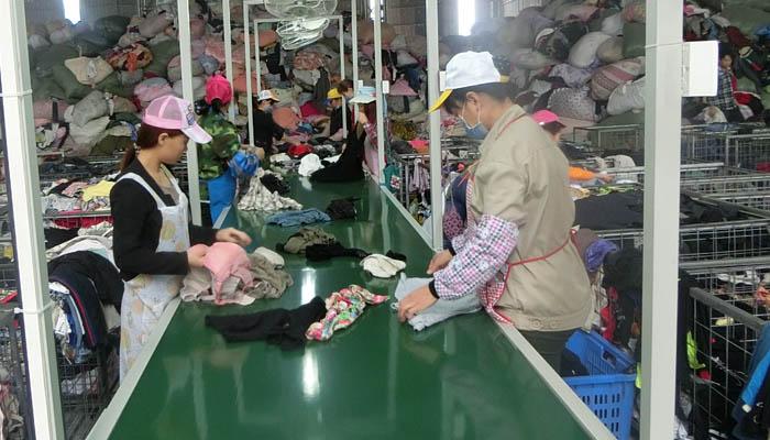 工人们在流水线上分拣旧衣服